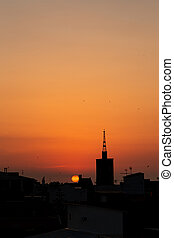 Orange summer sunrise, roof top view of an old church tower above the city.