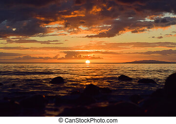 Orange sun setting in line with the seashore