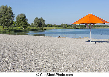 Orange sun umbrella on a bathing lake in Munich, Bavaria