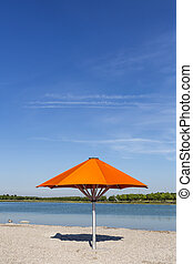 Orange sun umbrella on a bathing lake in Munich, Bavaria