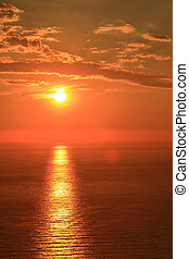 Orange sun with reflection on surface of the sea