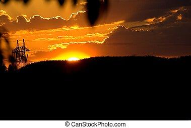 Orange Sunset - A sun setting behind a mountain ridge,...