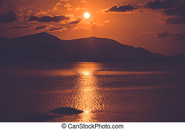 orange sunset at the sea with mountains silhouettes