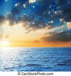orange sunset in dark sky over blue sea