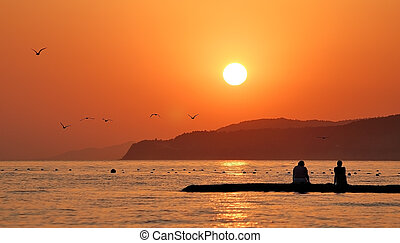 Orange sunset on sea with silhouettes of people and flying birds