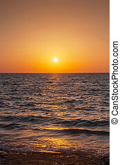 Orange sunset on the sea with the sun. Mykonos. Greece.