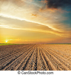 orange sunset over black agriculture field