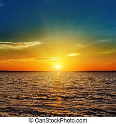 orange sunset over dark water