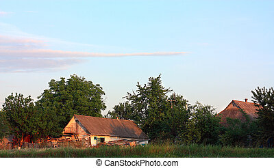 Orange sunset over the old village barn. Evening sun's...