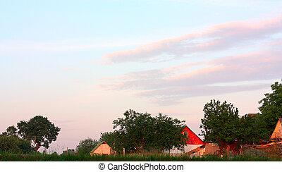 Orange sunset over the village. Evening sun's reflection