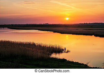 orange sunset over water in river