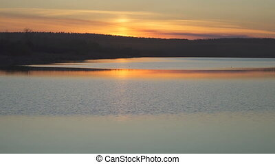 Orange sunset reflected on surface of lake on a summer day.