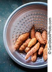 Orange sweet potato in a metal colander, close-up