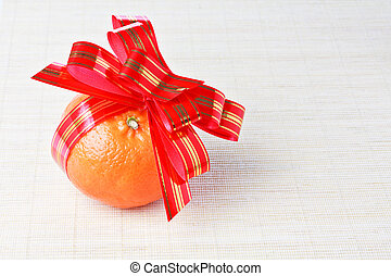 Orange tangerine with red goldish striped bow as a gift