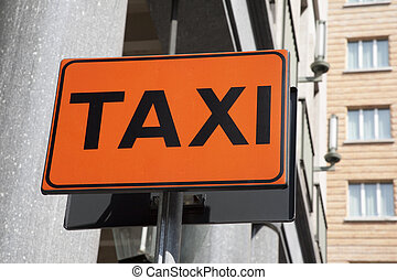 Orange taxi sign in urban setting