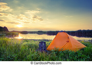Orange tent and backpack on the lake at sunset