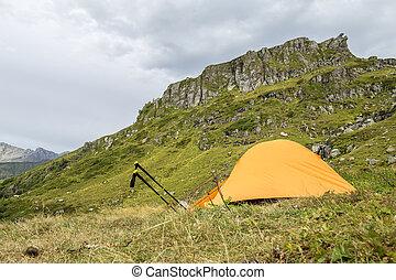 Orange tent in the mountains and trekking pole like a snail crawling