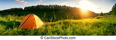 Orange tent in the mountains on a green meadow