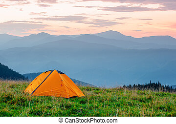 Orange tent on meadow in mountains under pink sky