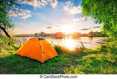 Orange tent on the lake at sunset