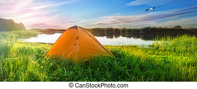 Orange tent on the shore of the lake
