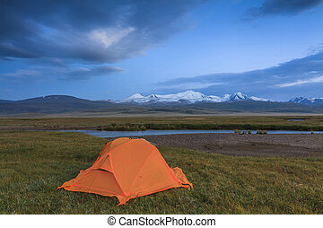 Orange tent on the shore of the lake on a background of mountains.