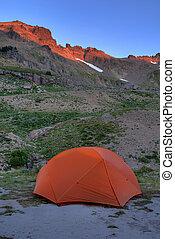 Orange tent, sunrise in the mountains