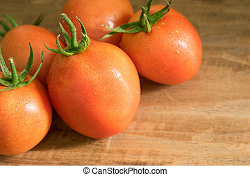 Orange tomatoes on wood background, with space for text