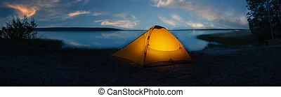 Orange tourist tent illuminated from inside on shore of lake under sunset sky