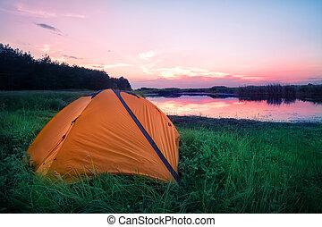 Orange tourist tent in green grass on the lake shore