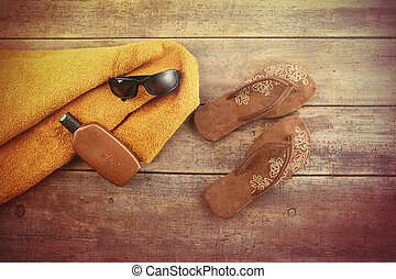 Orange towel and beach items on wood