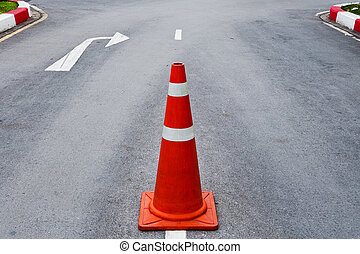 Orange traffic cone on asphalt road with white arrow to turn...