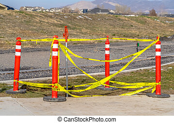 Orange traffic poles with yellow caution tape surrounding a hole on the ground
