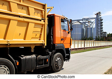 orange truck on the territory of grain storage in sunny weather harvesting