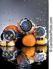 An abstract picture of designer watches and oranges submerged in water