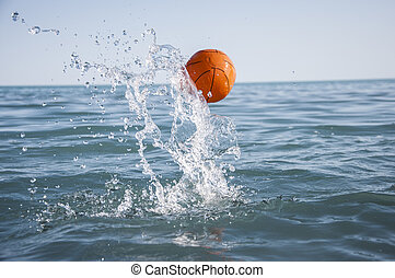 orange water polo ball on blue water background