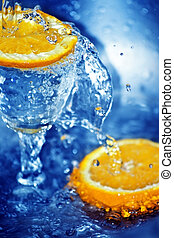 Orange waterfall - Two slices of orange and a glass in blue ...