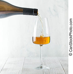 Orange wine is poured into a glass from a bottle. Copy space.