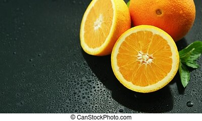 Orange with leaf on wet table - From above closeup shot of...