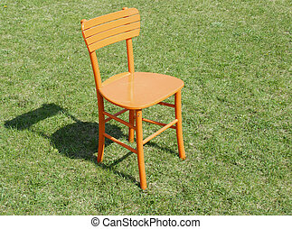 Orange wooden chair on grass
