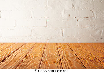 orange wooden tabletop and white wall with bricks