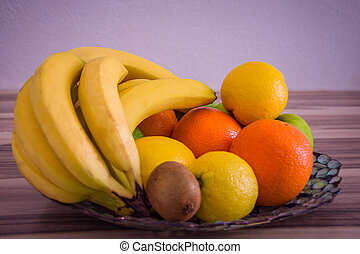 Oranges and lemons on a bowl between other fruits