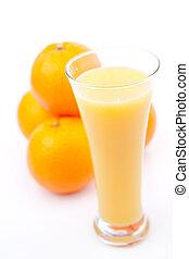 Oranges behind a glass of orange juice