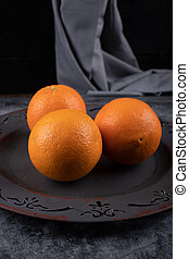 Oranges in a rustic dark plate on the dark background.