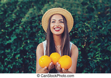 Oranges in the hands of the girl.