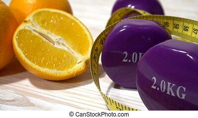 Oranges, juice, dumbbells and measuring tape on wooden...