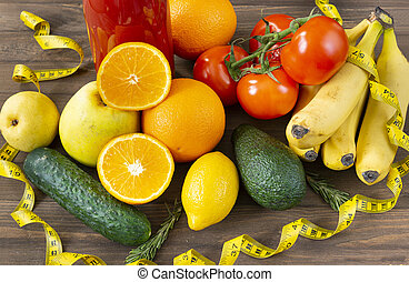 oranges, lemon, apples, bananas, tomatoes, avocado, cucumbers, rosemary, a bottle of tomato juice on a brown wooden background, centimeter tape