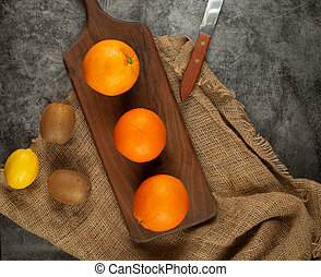 Oranges on a rustic wooden board. Top view.