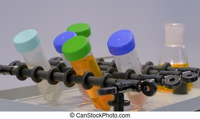 Chemistry, pharmaceutical, laboratory equipment concept. Slow motion: orbital shaker for mixing, shaking, blending biological samples in plastic vials at pharmacy factory, medical exhibition: close up