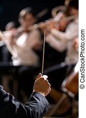Orchestra conductor on stage - Conductor directing symphony...
